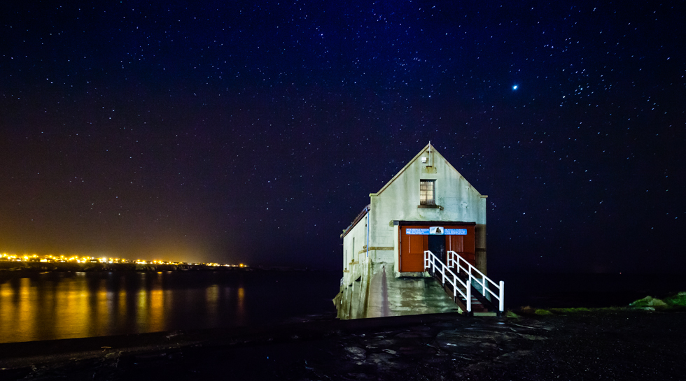 Lifeboat shed against the night sky